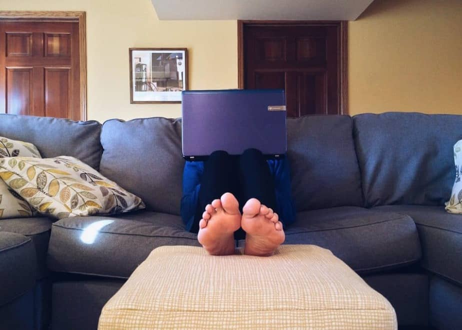 A person sitting on a couch with their feet up, with a laptop resting on their knees which is blocking their face.