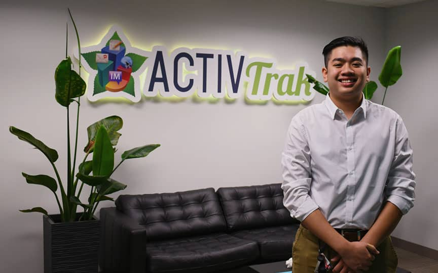 Tim Smaller standing in front of a black couch with plants on either side and the ActivTrak logo on the wall.