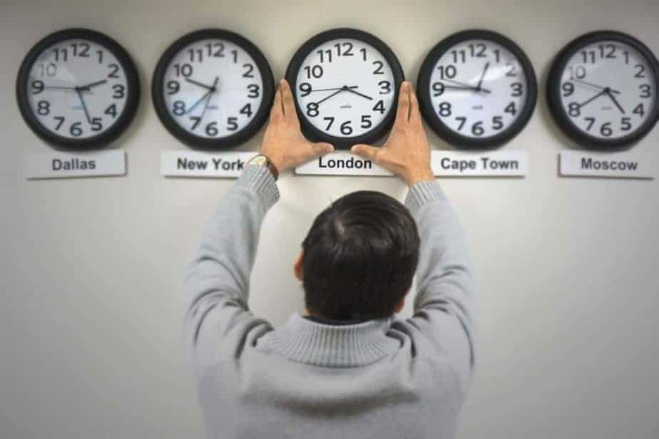 Five clocks in a row on a wall, each with a different city's name under it. A man adjusts the central one.