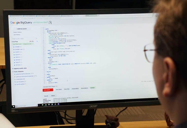 Seen from behind, a man looking at a computer monitor showing html code.