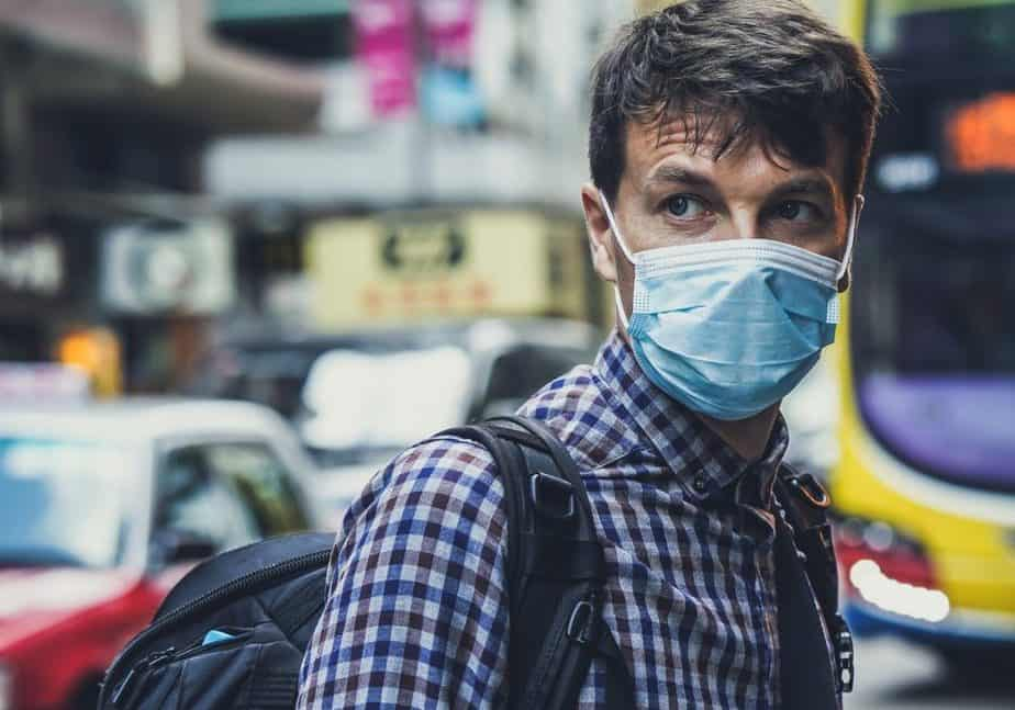 A man wearing a surgical mask and a plaid shirt, in front of city traffic.