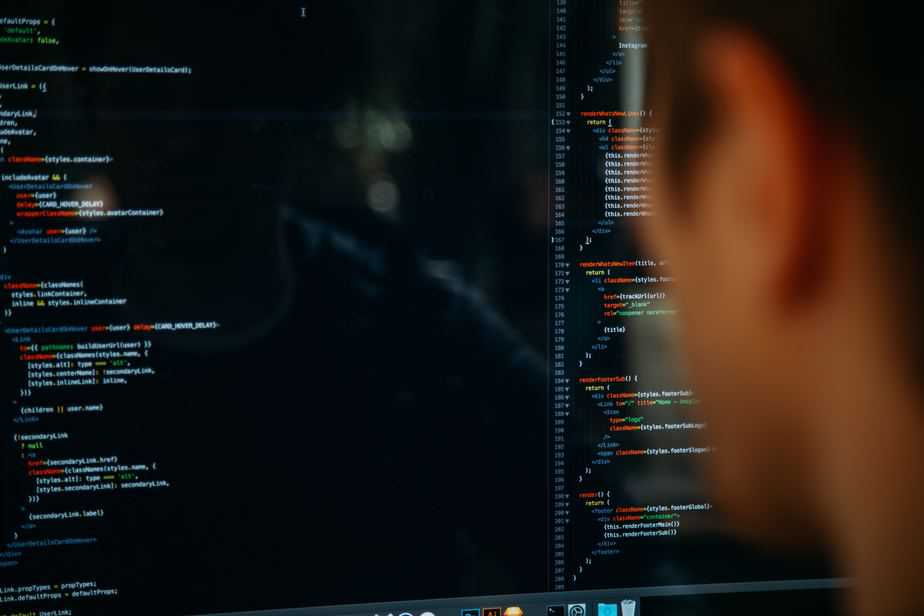 Seen from behind, a person looking at many lines of code on a large computer monitor.