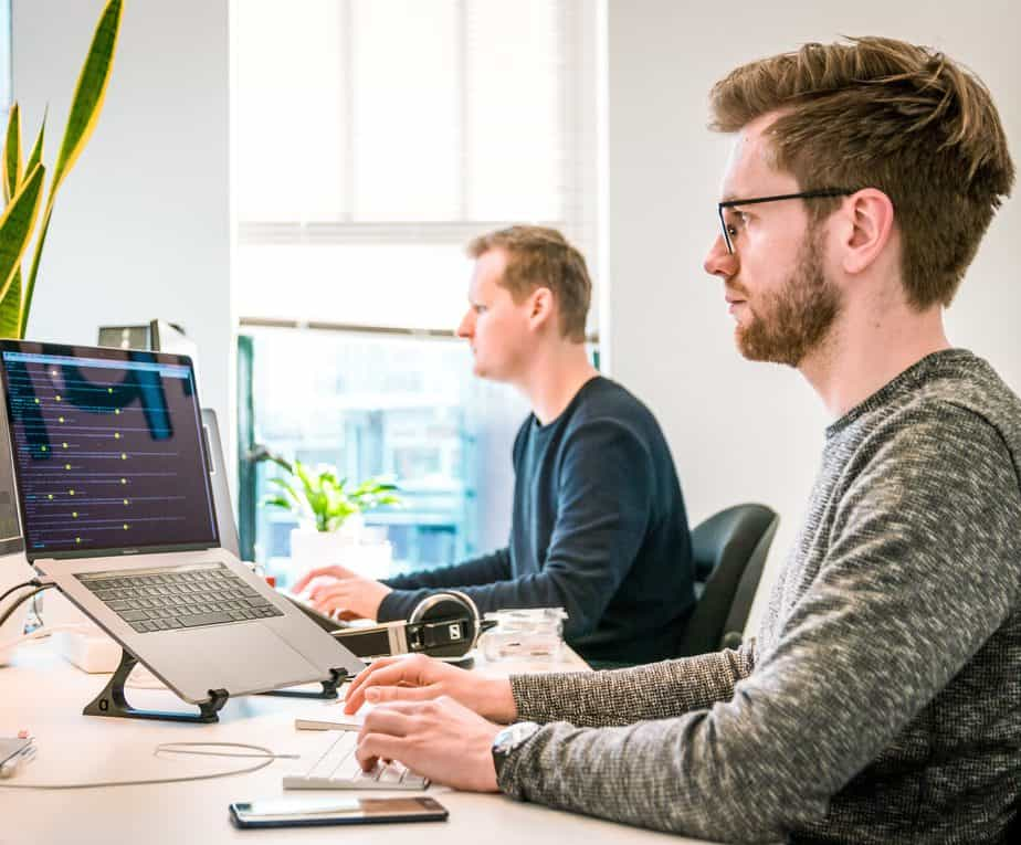 2 men working at a table on their computers.