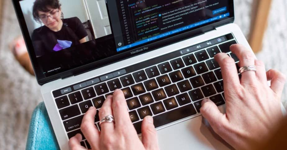 A woman's hands typing on a laptop keyboard.