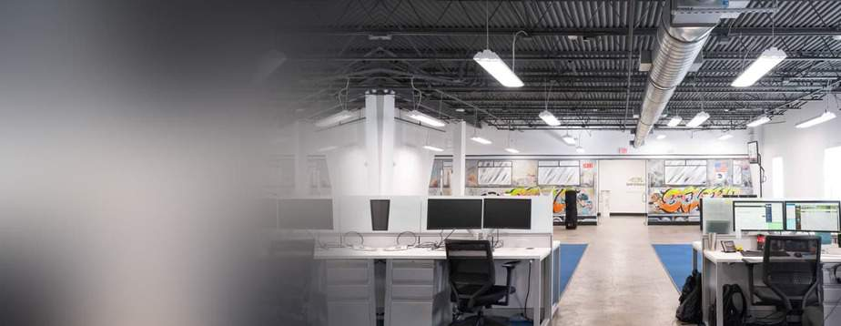 Several desks with two monitors on each, in an open warehouse used at office space.