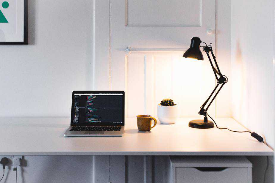 A desk in a home office with a laptop, lamp, plant and mug on it.
