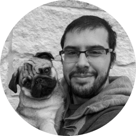 A black and white photo of a man in a hoodie holding a Pug dog.