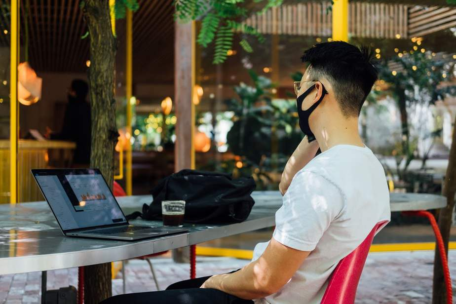 Alt: Remote worker sitting outdoors at a table with his laptop.