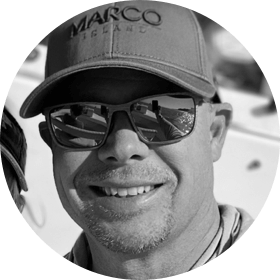 Neil Garret who is wearing a baseball cap and sunglasses and is smiling.