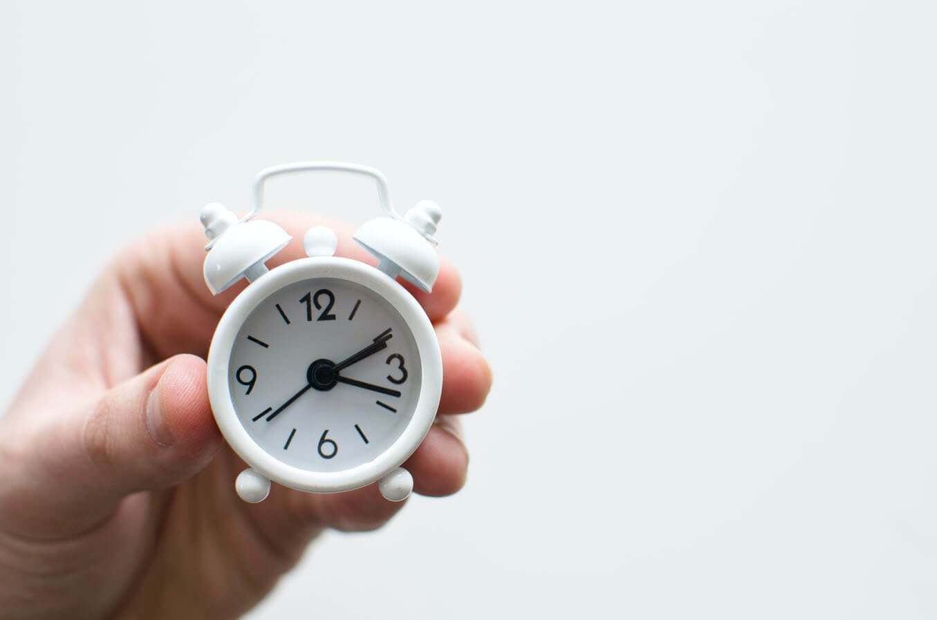 Image of a hand holding a clock